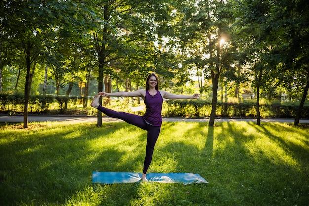 Mooie vrouw die yoga op een mat in het park doet bij zonsondergang