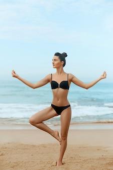 Mooie vrouw die yoga op het strand doet. meisje beoefent yoga en mediteert. actieve levensstijl. gezond en yogaconcept.
