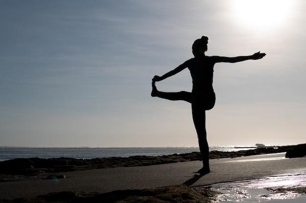 Mooie vrouw die yoga op het strand doet