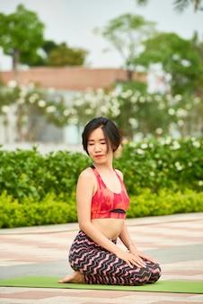 Mooie vrouw die yoga op mat doet