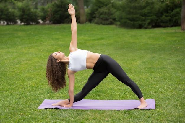 Mooie vrouw die yogaoefeningen doet bij park