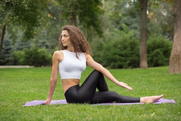 Mooie vrouw die yogaoefeningen doet
