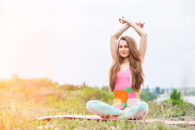 Mooie vrouw die yogaoefeningen op aardlandschap doet