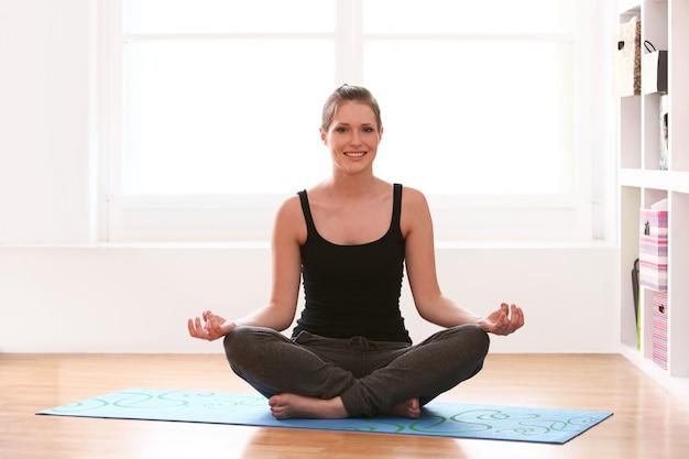 Mooie vrouw die yogaoefeningen thuis doet