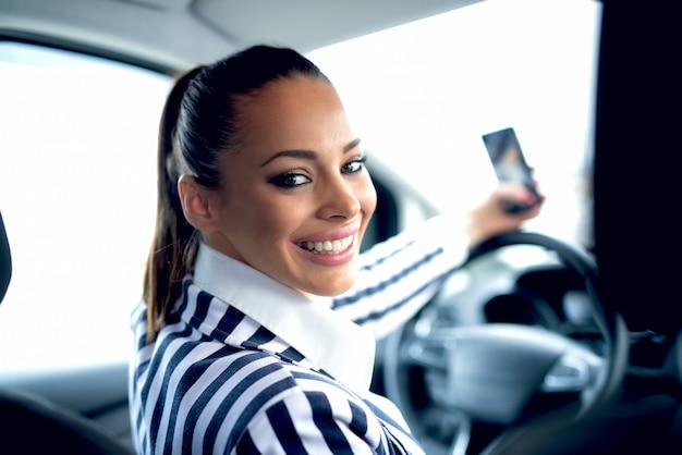 Mooie vrouw die zelfportret maken bij auto.