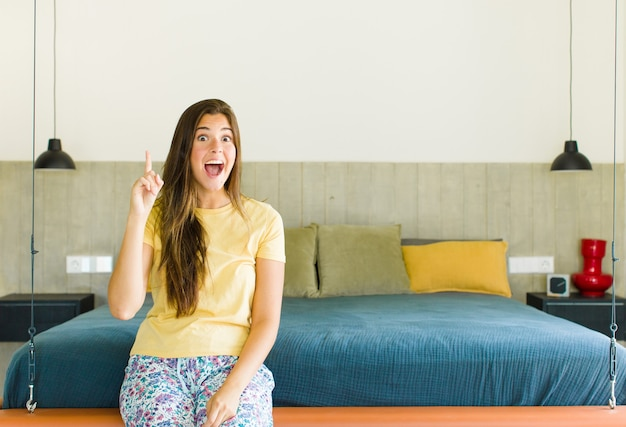 Mooie vrouw die zich als een blij en opgewonden genie voelt na het realiseren van een idee, opgewekt de vinger opstekend, eureka!