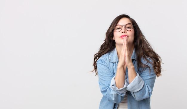 Mooie vrouw die zich bezorgd, hoopvol en religieus voelt, trouw bidt met ingedrukte handpalmen, smekend om vergiffenis