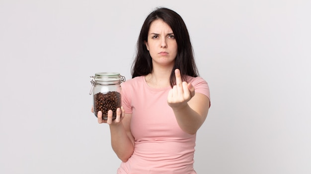 Mooie vrouw die zich boos, geïrriteerd, opstandig en agressief voelt en een fles koffiebonen vasthoudt