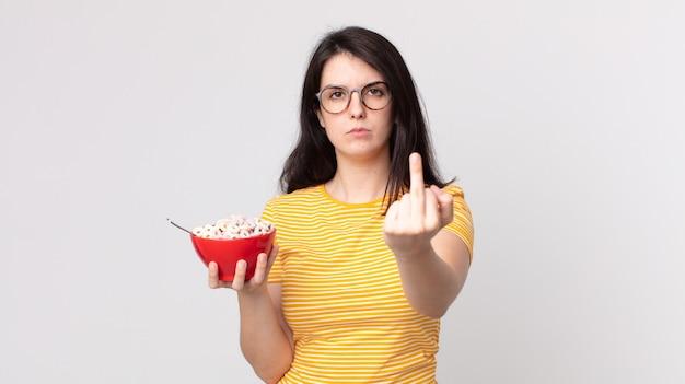 Mooie vrouw die zich boos, geïrriteerd, opstandig en agressief voelt en een ontbijtkom vasthoudt