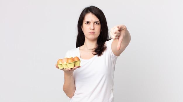 Mooie vrouw die zich boos voelt, duimen naar beneden laat zien en een eierdoos vasthoudt