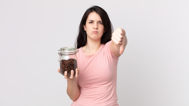 Mooie vrouw die zich boos voelt, duimen naar beneden laat zien en een fles koffiebonen vasthoudt