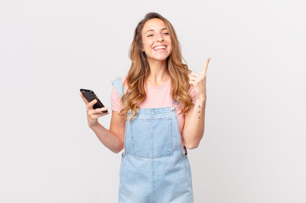 Mooie vrouw die zich een gelukkig en opgewonden genie voelt na het realiseren van een idee en het vasthouden van een smartphone