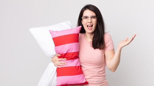 Mooie vrouw die zich gelukkig en verbaasd voelt over iets ongelooflijks dat een pyjama draagt en een kussen vasthoudt