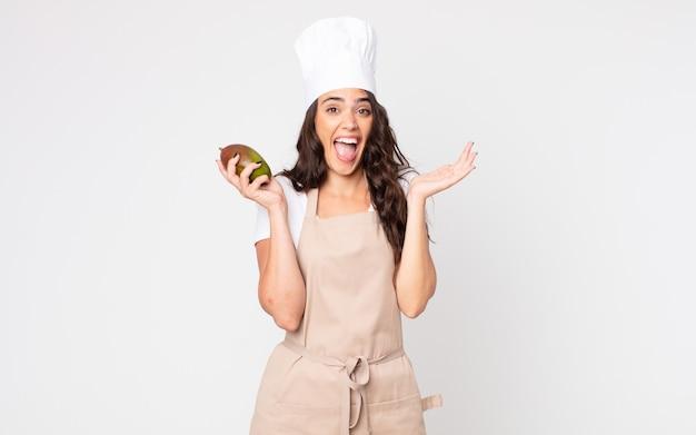 Mooie vrouw die zich gelukkig en verbaasd voelt over iets ongelooflijks dat een schort draagt en een mango vasthoudt