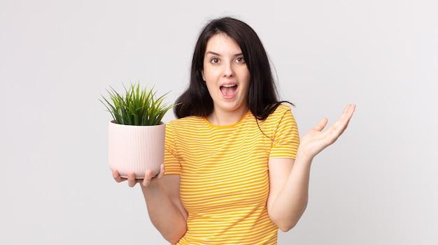Mooie vrouw die zich gelukkig en verbaasd voelt over iets ongelooflijks en een decoratieve plant vasthoudt