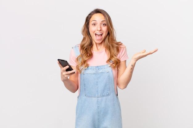Mooie vrouw die zich gelukkig en verbaasd voelt over iets ongelooflijks en een smartphone vasthoudt