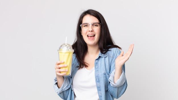 Mooie vrouw die zich gelukkig en verbaasd voelt over iets ongelooflijks en een vanillemilkshake vasthoudt