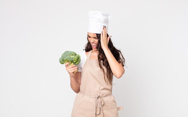 Mooie vrouw die zich gelukkig, opgewonden en verrast voelt, een schort draagt en een broccoli vasthoudt