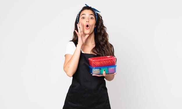 Mooie vrouw die zich gelukkig voelt, een grote schreeuw geeft met de handen naast de mond en tupperwares met eten vasthoudt