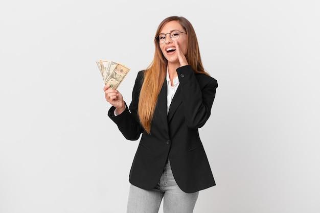 Mooie vrouw die zich gelukkig voelt, een grote schreeuw geeft met de handen naast de mond. zakelijk en dollars concept