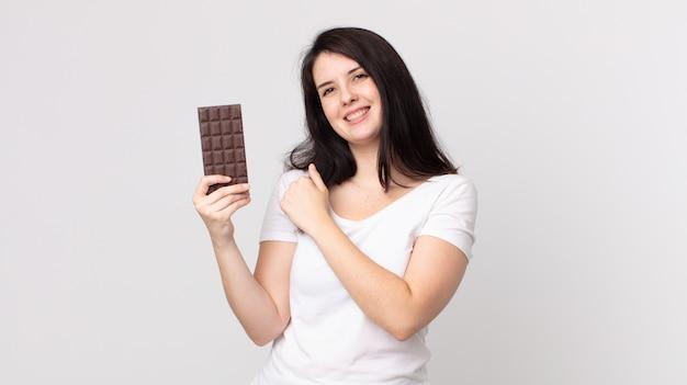 Mooie vrouw die zich gelukkig voelt en een uitdaging aangaat of een chocoladereep viert en vasthoudt