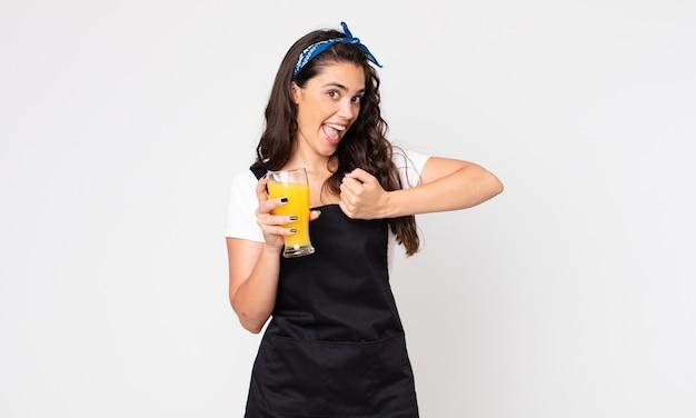 Mooie vrouw die zich gelukkig voelt en een uitdaging aangaat of een jus d'orangeglas viert en vasthoudt