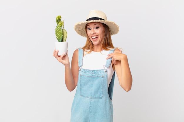 Mooie vrouw die zich gelukkig voelt en naar zichzelf wijst met een opgewonden en een decoratieve cactusplant vasthoudt
