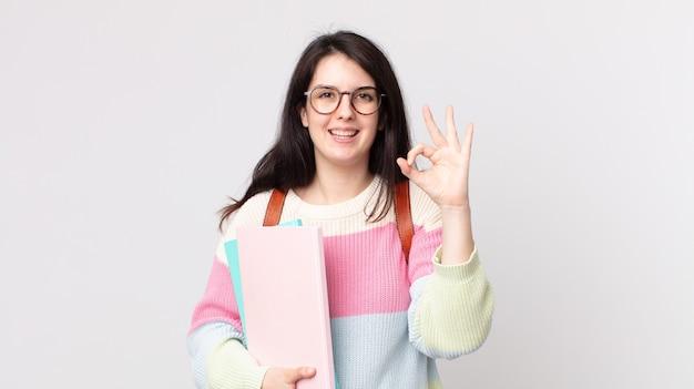 Mooie vrouw die zich gelukkig voelt, goedkeuring toont met een goed gebaar. universitair studentenconcept