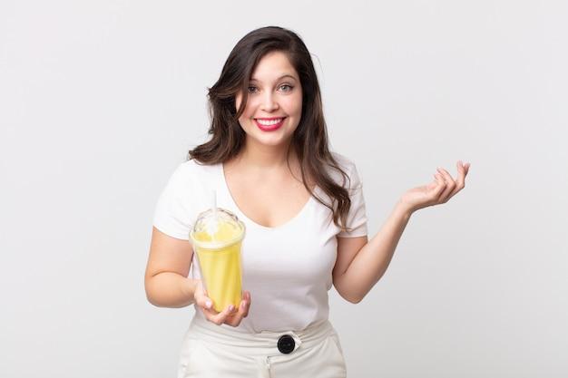 Mooie vrouw die zich gelukkig voelt, verrast een oplossing of idee realiseert en een vanillemilkshake vasthoudt