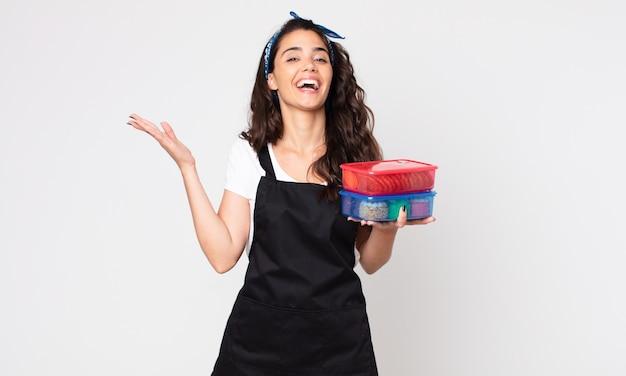 Mooie vrouw die zich gelukkig voelt, verrast een oplossing of idee realiseert en tupperwares met eten vasthoudt