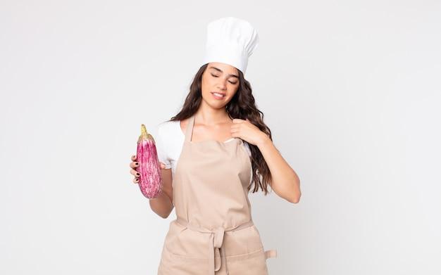 Mooie vrouw die zich gestrest, angstig, moe en gefrustreerd voelt, een schort draagt en een aubergine vasthoudt