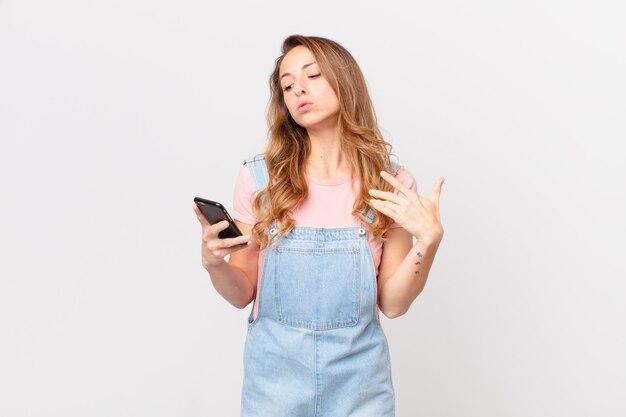 Mooie vrouw die zich gestrest, angstig, moe en gefrustreerd voelt en een smartphone vasthoudt