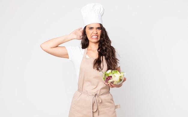 Mooie vrouw die zich gestrest, angstig of bang voelt, met de handen op het hoofd, een schort dragend en een salade vasthoudend
