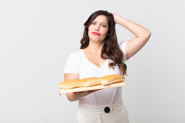 Mooie vrouw die zich gestrest, angstig of bang voelt, met de handen op het hoofd en een dienblad met broodjes