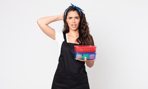 Mooie vrouw die zich gestrest, angstig of bang voelt, met de handen op het hoofd en tupperwares met eten vasthoudt