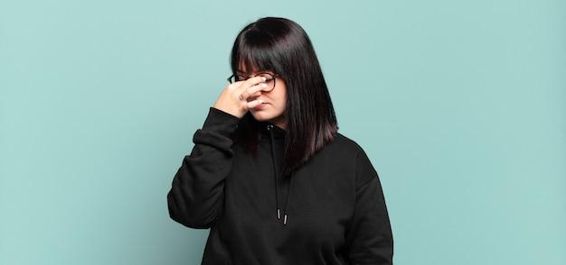 Mooie vrouw die zich gestrest, ongelukkig en gefrustreerd voelt, het voorhoofd aanraakt en lijdt aan migraine of ernstige hoofdpijn