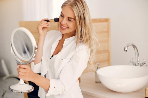 Mooie vrouw die zich in een badkamers bevindt