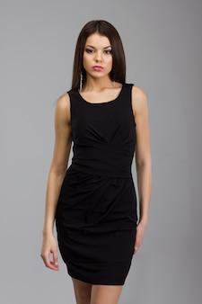 Mooie vrouw die zich in een zwarte kleding bevindt