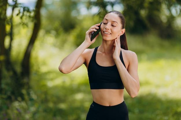 Mooie vrouw die zich in het park bevindt en een smartphone spreekt openlucht.