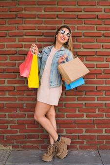 Mooie vrouw die zich met het winkelen zakken bij bakstenen muur bevindt