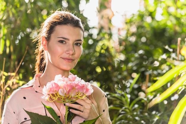 Mooie vrouw die zich met roze in hand bloem bevindt