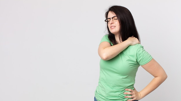 Mooie vrouw die zich moe, gestrest, angstig, gefrustreerd en depressief voelt, last heeft van rug- of nekpijn