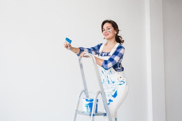Mooie vrouw die zich op de ladder bevindt en muren schildert.