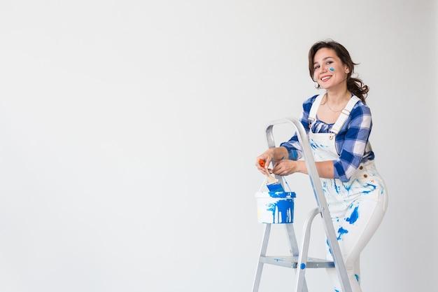 Mooie vrouw die zich op de ladder bevindt en verf over witte achtergrond met exemplaarruimte mengt.