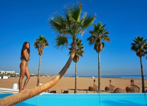 Mooie vrouw die zich op gebogen palm bevindt