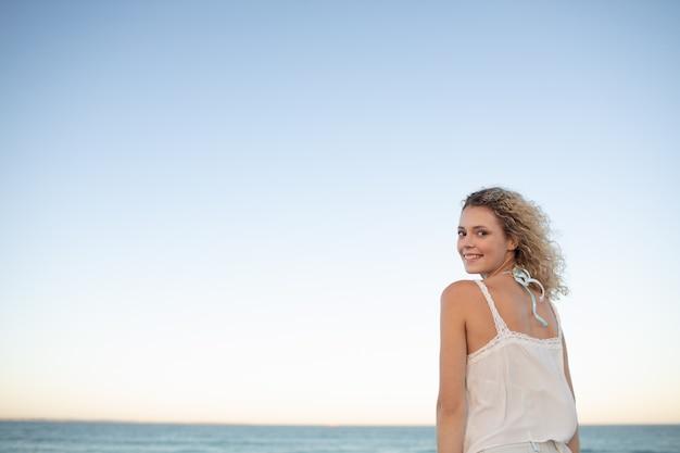 Mooie vrouw die zich op het strand bevindt