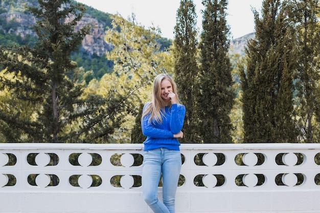 Mooie vrouw die zich op terras dichtbij bos bevindt