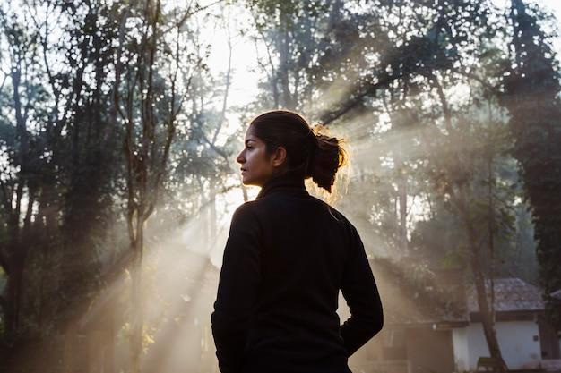 Mooie vrouw die zich op voorzijde van een verbazende zonsopgang in het hout bevindt. nationaal park in thailand. trekking en toerisme in azië. nieuwe ervaring in contact met de natuur. gezonde spirituele levensstijl.