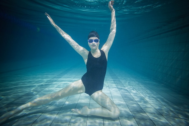 Mooie vrouw die zich uitstrekt onder water bij het zwembad
