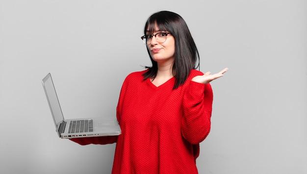 Mooie vrouw die zich verbaasd en verward voelt, twijfelt, weegt of verschillende opties kiest met een grappige uitdrukking